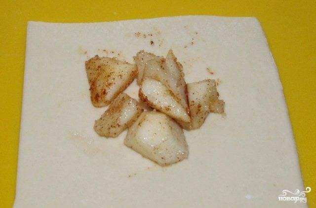 Яблоки чистим от кожурки и рубим на кубики. Смешиваем с корицей и сахаром. Начинку выкладываем на порезанное на квадратики и предварительно раскатанное тесто.