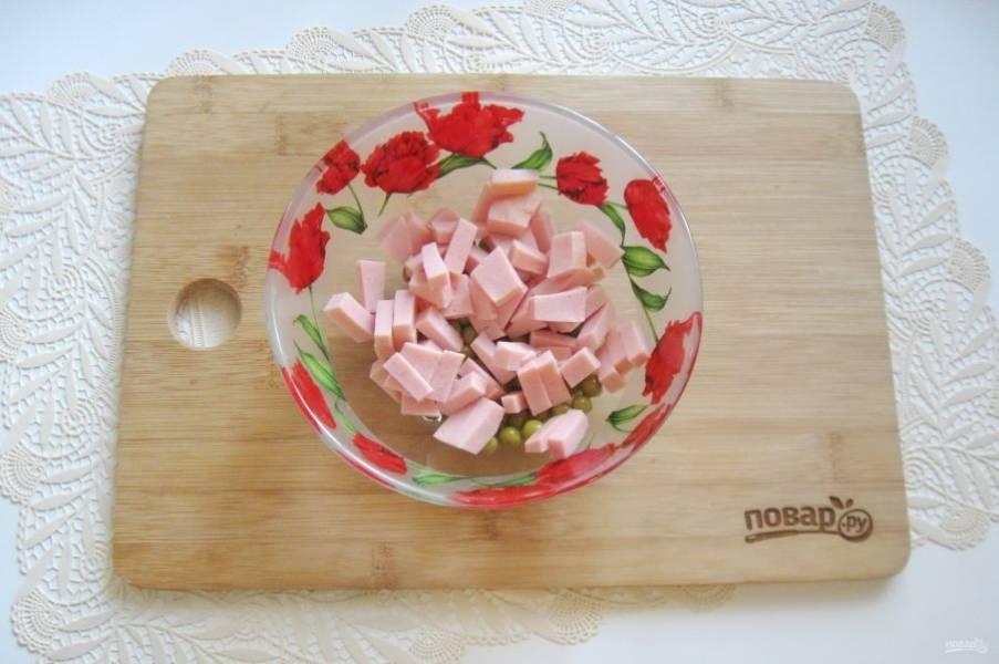 Колбасу нарежьте мелким кубиком и добавьте в салат.