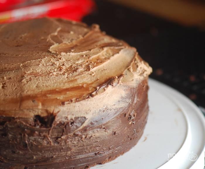 2. Для глазури: взбейте мягкое сливочное масло и сыр, постепенно введите всю сахарную пудру, предварительно просеив. Тонкой струйкой влейте молоко, ванильный экстракт. В отдельной тарелке растопите шоколад, затем остудите его и введите в масляный крем, перемешайте. Перемажьте два бисквитных коржа кремом, а также смажьте бока и верхушку.