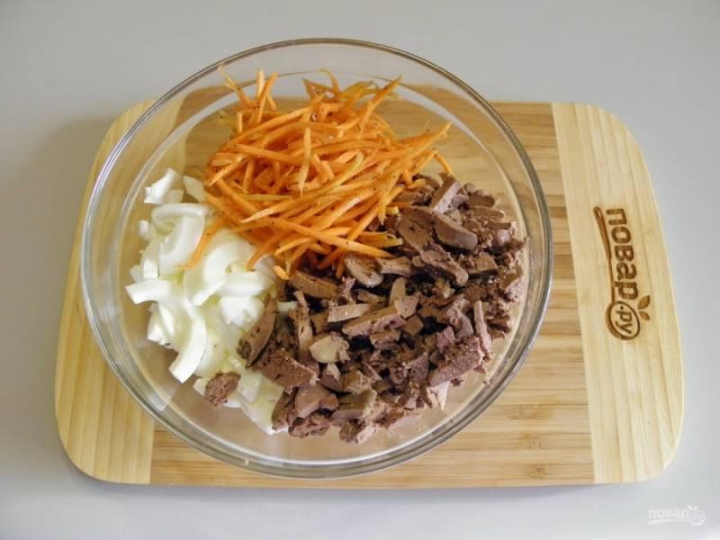 Отделите желтки от белков. Желтки оставьте для украшения салата, также отложите не большой кусочек печени. Остальные продукты порежьте соломкой. Сложите в салатник.