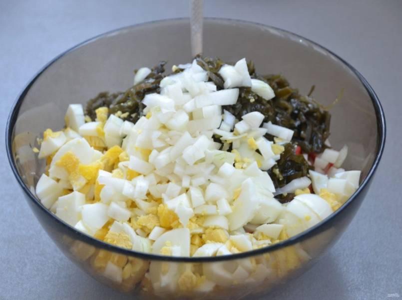 Мелко нарежьте отварные яйца и тоже добавьте их в салат. Слейте маринад с лука, выложите маринованный лук в салатник.