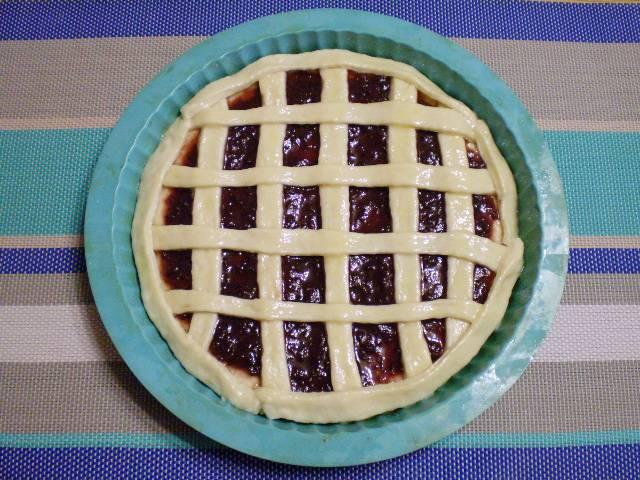 8. Вторую часть тонко раскатайте и нарежьте полосками. Полоски разложите по пирогу. Смажьте желтком. Отправьте в теплое место на 20 минут для подъема. После чего выпекайте в духовке при 180 градусах 35-40 минут.