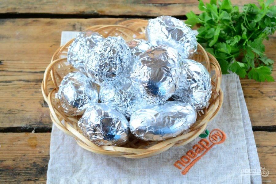 Каждую картофелину заверните в фольгу, выложите на противень и запекайте в духовке при температуре 180 градусов 30-40 минут. Она должна быть не просто готовой, а даже слегка разваливаться. Конечно, здесь все зависит от сорта, картофель с большим содержанием крахмала останется плотным.