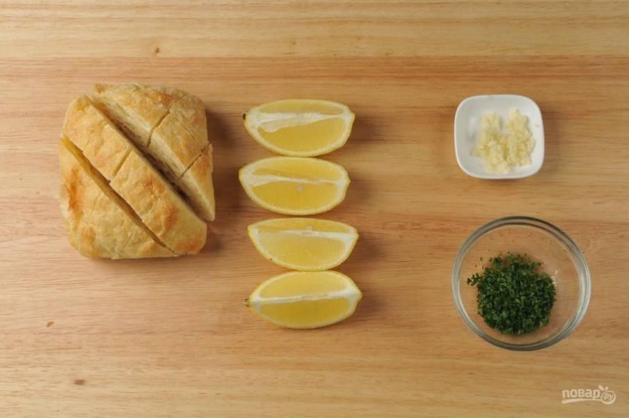 1. Для начала мелко нарубите чеснок и петрушку. Лимон разрежьте на 4 дольки. На чиабатте сделайте по 3 разреза по обеим диагоналям.