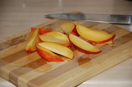 Промойте и порежьте персики дольками, удалив косточки.