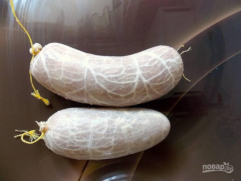 Замочите синюгу согласно инструкции. Набейте ее плотно фаршем. Завяжите туго концы. Отправьте колбасу в холодильник на сутки.