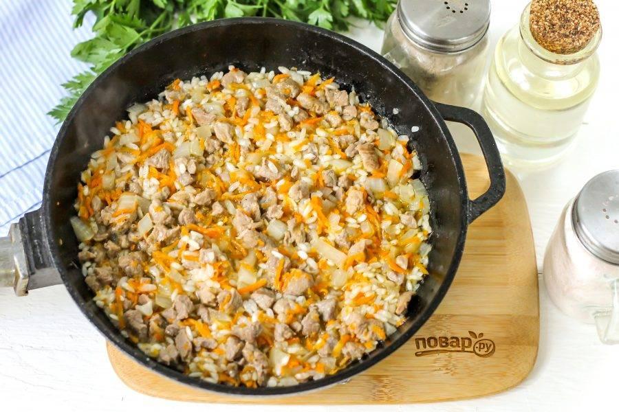 Влейте 0,5 стакана горячей воды и отварите рис в мясном бульоне до полуготовности. Посолите начинку и выключите нагрев. Дайте ей слегка остыть.