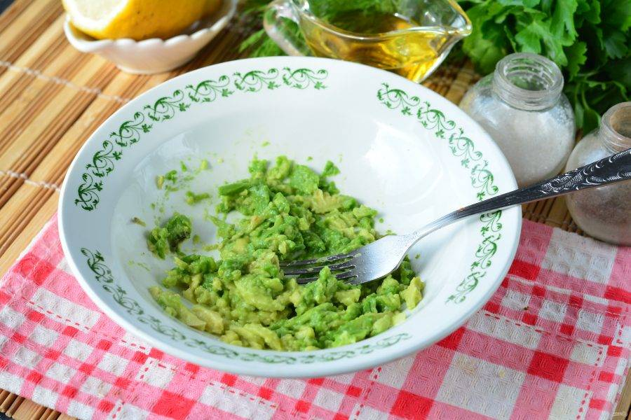 Извлеките косточку из авокадо, достаньте мякоть ложкой и выложите в глубокую тарелку. Разомните авокадо вилочкой.