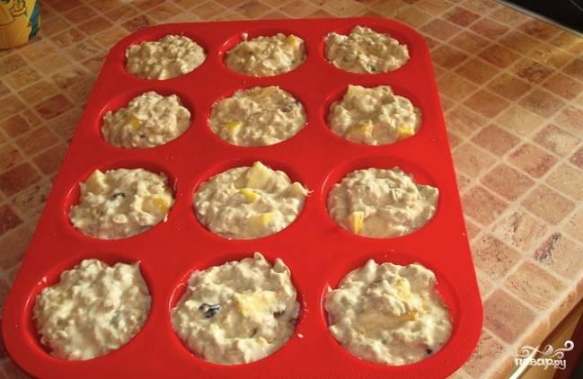 Форму для маффинов смажьте растительным маслом, чтобы их было легче вынимать. При помощи столовой ложки разложите тесто по формочкам. Разогрейте духовку до 180 градусов.