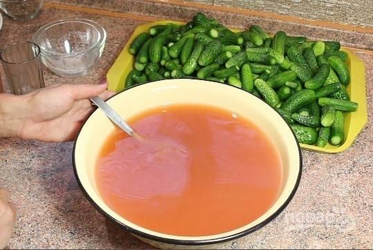 2. Для приготовления маринада соедините соль, сахар, уксус, кетчуп и воду. Доведите до кипения, постоянно помешивая. Снимите сразу с огня. В баночки разложите зелень, огурчики, чеснок.