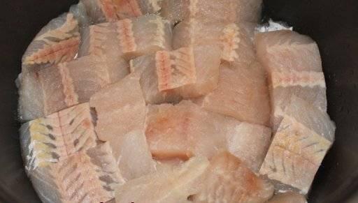 2. Нарезаем филе, солим и перчим по вкусу. Теперь дно мультиварки смазываем маслом и выкладываем рыбу.