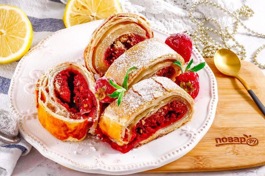Аккуратно присыпьте штрудель сахарной пудрой, разрежьте на части и выложите их на тарелку. Подайте с шариком мороженого, ягодами, горячим напитком.
