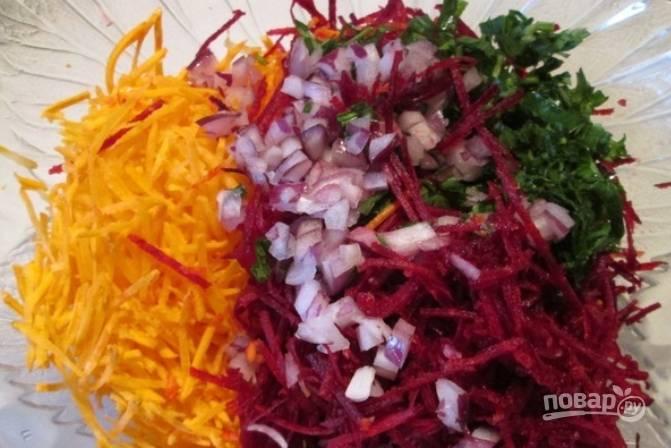 Овощи промываем и очищаем. Трем на терке морковь и свеклу. Измельчаем зелень и красный лук. Соединяем овощи в салатнице.