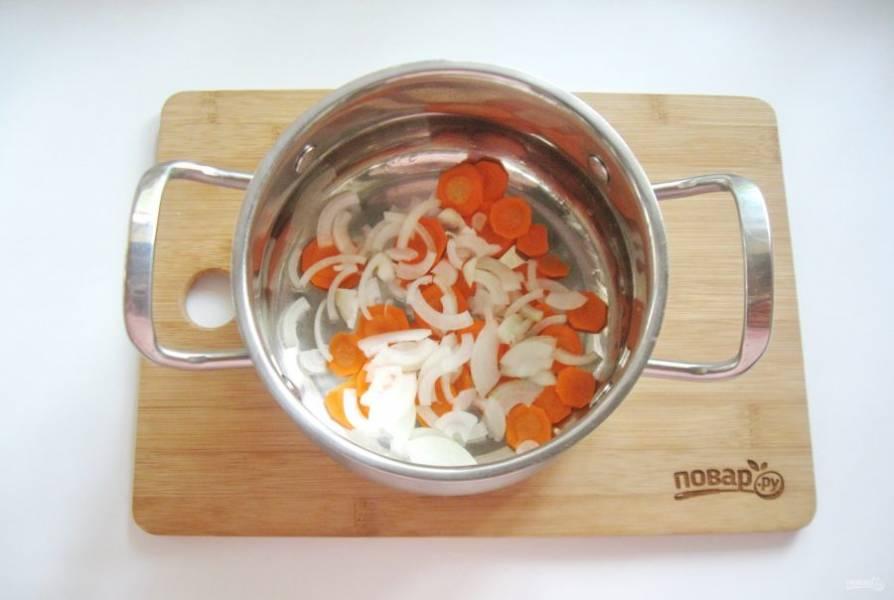 Морковь и лук очистите, помойте и нарежьте произвольно. Выложите в кастрюлю с толстым дном.
