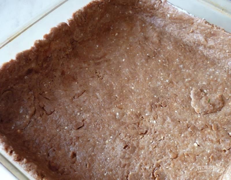 Раскатайте тесто в пласт. Он не должен быть слишком тонким. Тесто будет раскатываться легко, так как оно должно получиться мягким и податливым. Смажьте любую удобную для вас форму для запекания растительным маслом, выложите в нее раскатанное тесто, сделав высокие бортики.