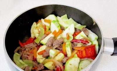 Разогреваем в сотейнике растительное мясо, обжариваем на нем лук и морковь, через пару минут добавляем порезанную кусочками отварную говядину, кабачки и болгарский перец. Можно влить немного воды. Также добавляем острый перец целиком и соль. Готовим, пока кабачки не станут мягкими и сочными.