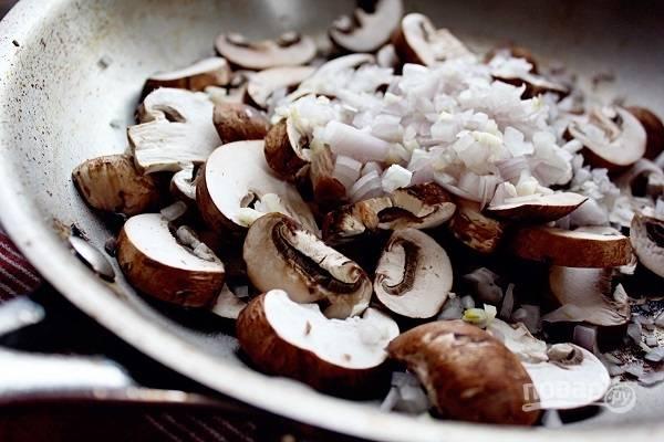 4. Мясо снимите со сковороды и переложите на теплую тарелку. Добавьте еще немного масла и выложите лук, чеснок, измельченные грибы.
