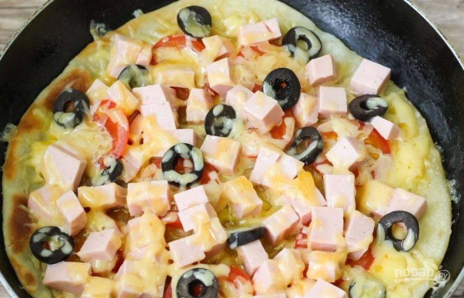 Присыпьте пиццу остатками сыра. Накройте сковороду крышкой и поджаривайте на медленном огне десять минут, чтобы сыр расплавился, а корж подрумянился.