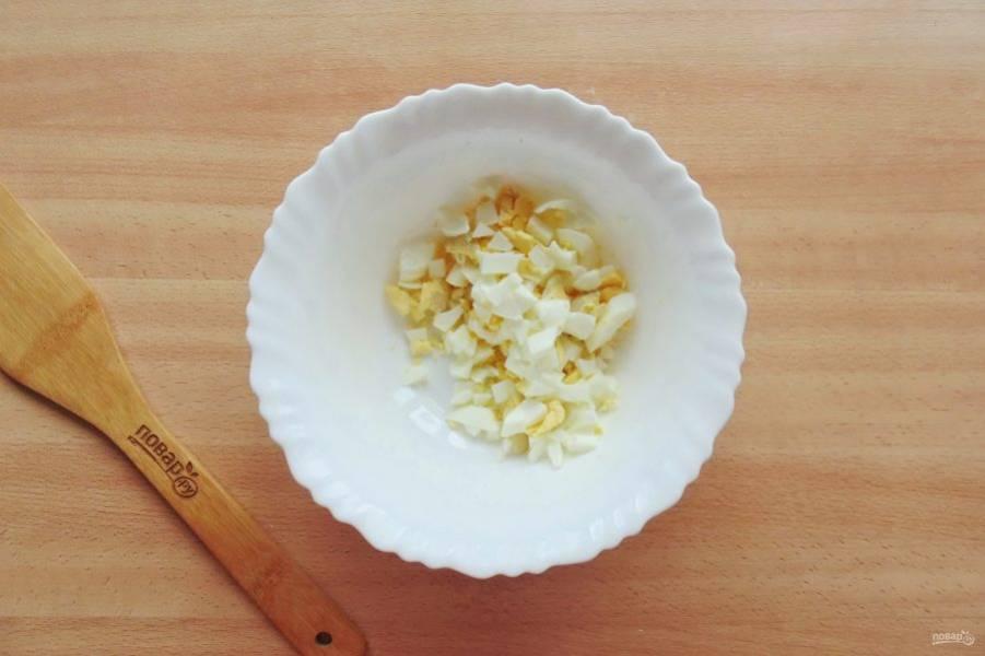 Яйца сварите вкрутую, охладите и очистите. Нарежьте небольшими кубиками и выложите в салатник.