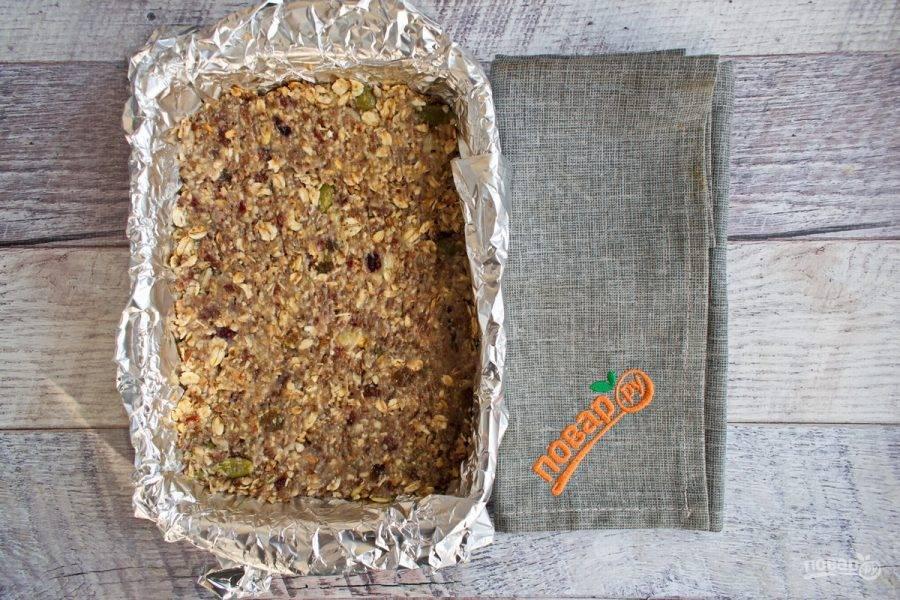 Форму для запекания застелите фольгой, формируя бортики. Выложите готовую массу, хорошо утрамбуйте. Поставьте запекаться в духовку на 15 минут при 180 градусах.