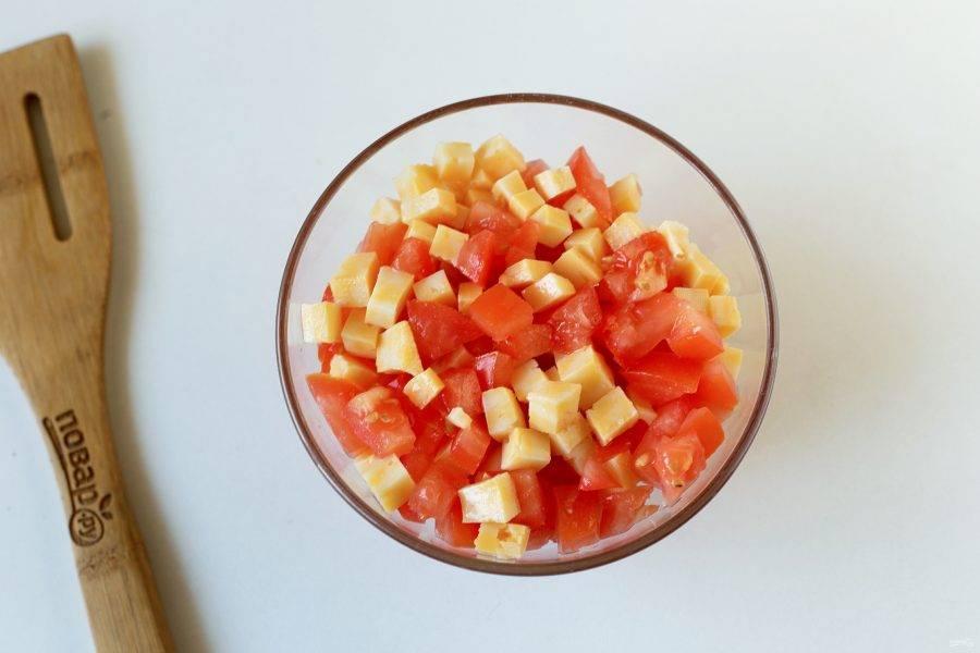 Для начинки соедините нарезанный кубиками сыр и помидор.