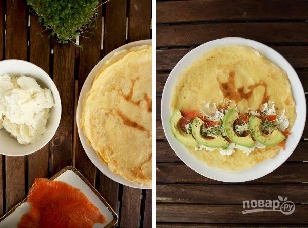 2. Очистите и нарежьте тонкими ломтиками авокадо, нарежьте семгу. Выложите блинчик на рабочий стол. Смажьте сыром, сверху разместите пару ломтиков рыбы и авокадо. Присыпьте перцем, дополните зеленью по желанию.