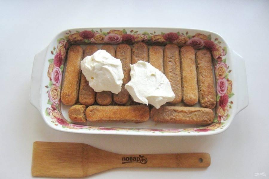 Половину крема выложите на слой печенья.