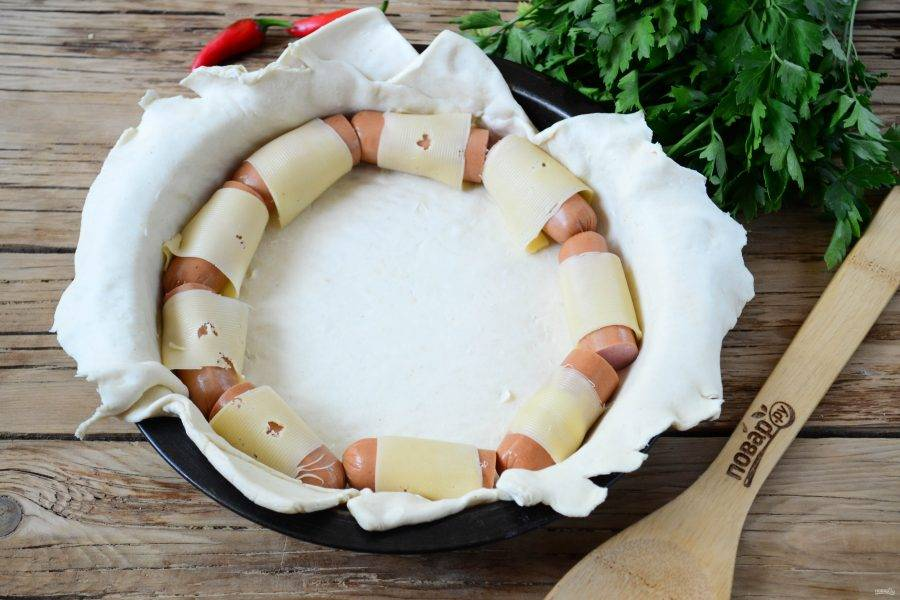 Каждую сосиску разрежьте пополам и оберните тонким ломтиком сыра. Выложите половинки сосисок по кругу на тесто по краю бортика.