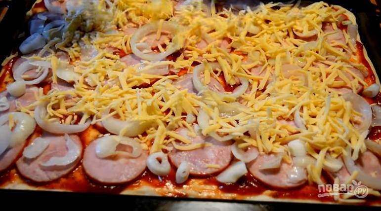 7. Выложите колбасу, затем маринованный лук. Засыпьте всё тертым сыром и сверху выложите кусочки моцареллы.