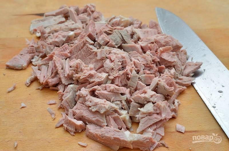 1.В кастрюлю выложите мясо и залейте его 4 литрами воды, отправьте на огонь и варите около двух часов, затем удалите и остудите мясо, нарежьте его кусочками. Переложите мясо в бульон и верните его на огонь.