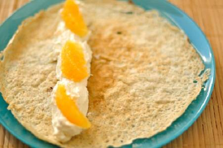 5. Для приготовления блинчиков необходимо взбить яйца с солью и сахаром. Затем влить примерно половину молока и всыпать муку. Тщательно взбить тесто и развести оставшимся молоком до необходимой консистенции. Добавить растительное масло и жарить тоненькие блинчики. Когда они готовы, на блинчик выложить немного маскарпоне и несколько кусочков апельсина.