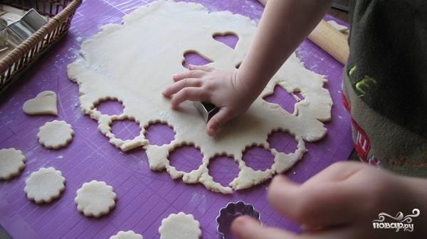Духовку выставьте на сто восемьдесят градусов. Пока та греется, раскатайте тесто из холодильника в пласт толщиной около одного сантиметра. Затем при помощи разных формочек вырежете будущие пряники.