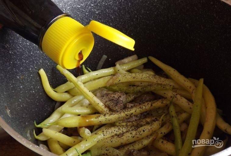 Поперчите и посолите ингредиенты по вкусу. Влейте соевый соус, перемешайте все. Затем накройте сотейник крышкой и тушите блюдо до готовности на медленном огне, пока фасоль не станет мягкой. За минуту до готовности положите в сотейник рубленый чеснок и кунжутные семечки.