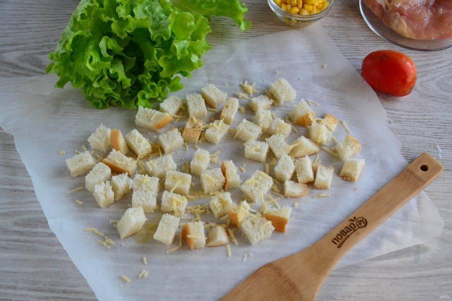 Выложите кубики хлеба на пергамент, сбрызните растительным маслом и присыпьте небольшим количеством натертого сыра. Отправьте в духовку, разогретую до 160 градусов и подсушите в течение минут 5-10. Время может варьироваться, зависимо от типа духовки и самого хлеба.