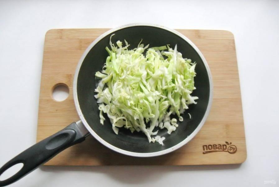 Капусту мелко нарежьте и добавьте в сковороду к луку.