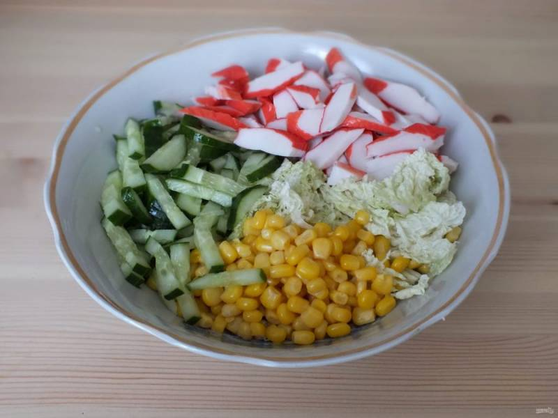 Возьмите глубокий салатник. Руками нарвите помельче пекинскую капусту. Огурец нарежьте крупной соломкой. Переложите овощи в салатник, добавьте кукурузу и крабовые палочки, нарезанные крупными кусочками.