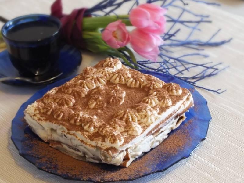 Перед подачей, достаньте торт из холодильника. Извлеките из формы, уберите пищевую пленку, переложите на блюдо и посыпьте сверху какао. Торт готов.