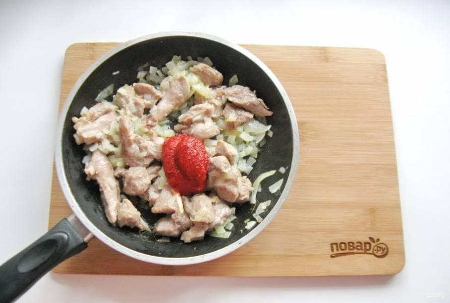 Обжарьте лук с мясом в течение 6-7 минут, перемешивая. Добавьте томатную пасту.
