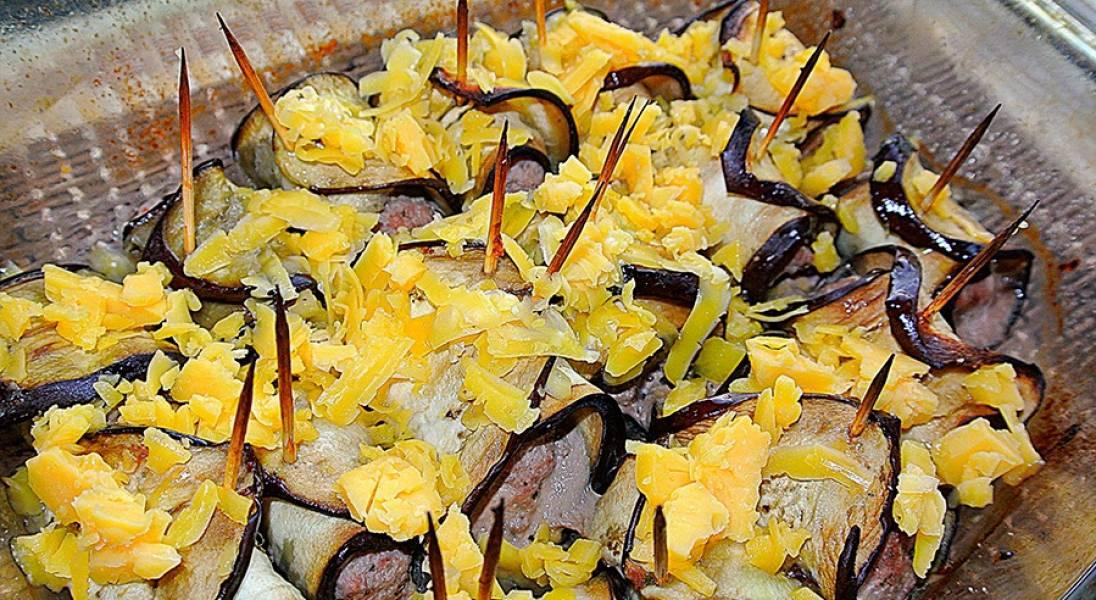 За пару минут до приготовления, посыпьте рулетики тертым сыром.
