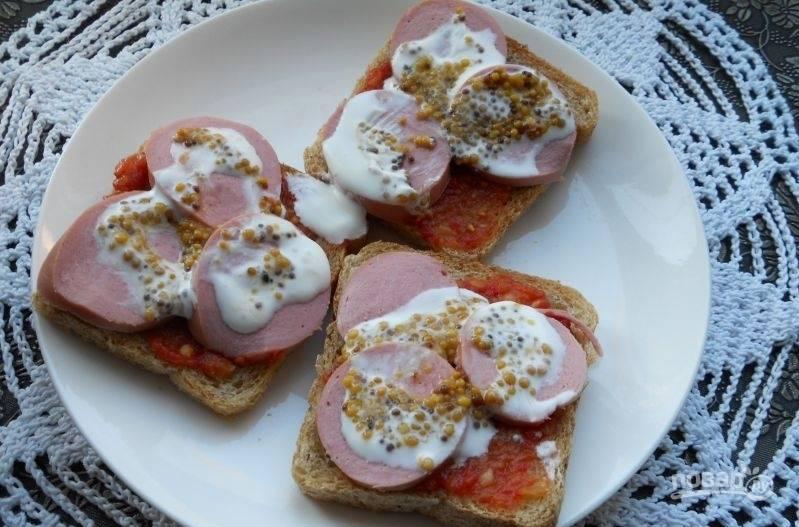 На соус уложите кружки колбасы или сардельки. Сверху смажьте бутерброды сметаной и горчицей.