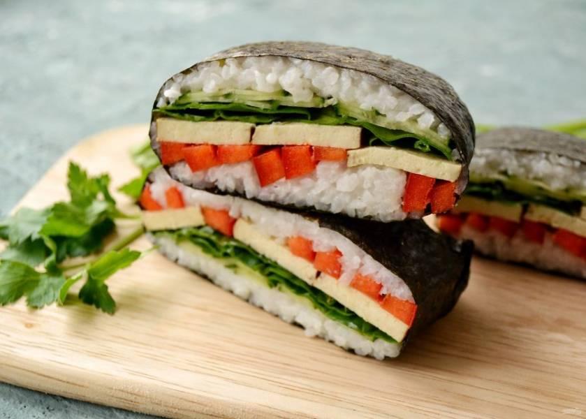 Острым ножом разрежьте онигирадзу поперёк. После каждого рисового сэндвича промывайте нож в холодной воде, тогда получится максимально красивый результат. Подавать онигирадзу лучше всего вместе с терияки или соевым соусом. Приятного аппетита!