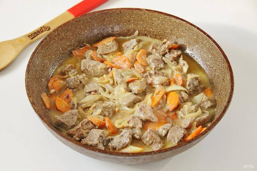 Добавьте муку, перемешайте и влейте примерно чуть меньше стакана кипятка. Накройте сковороду крышкой и на небольшом огне тушите мясо примерно 40 минут или до тех пор, пока жидкость не испарится.