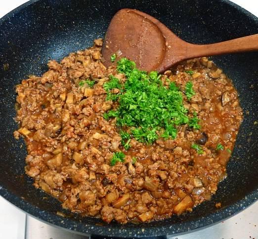 5. Посолить и поперчить все по вкусу, добавить специи и 1 ложку томатного соуса. Потушить до готовности, а затем добавить измельченную петрушку и снять с огня. Остудить начинку.