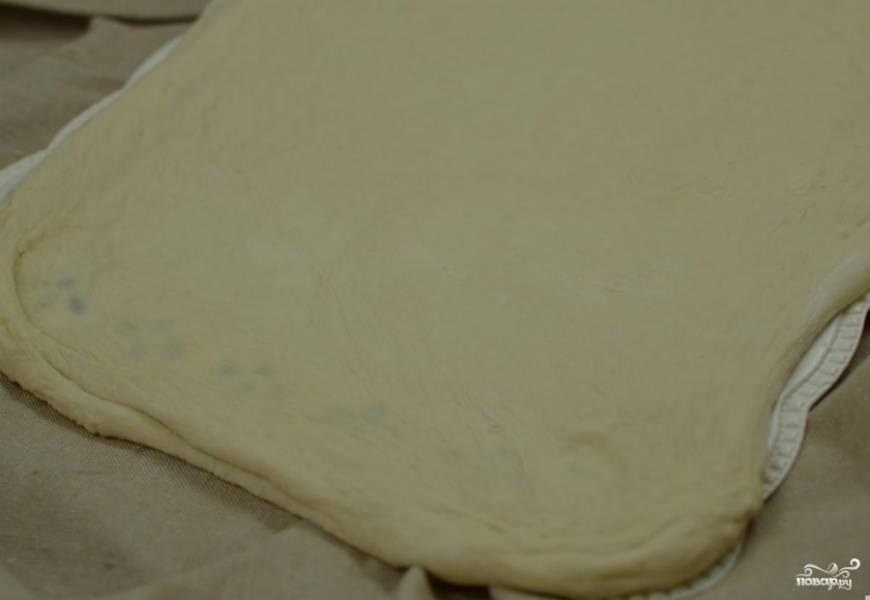 Затем тесто делим на две равные части, раскатываем в прямоугольник и смазываем внутреннюю часть сливочным маслом (50 гр).