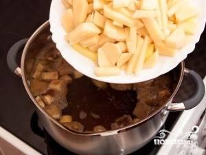 Картофель помойте, почистите и нарежьте брусочками или кубиками. Добавьте его в бульон к грибам и варите 8 минут.