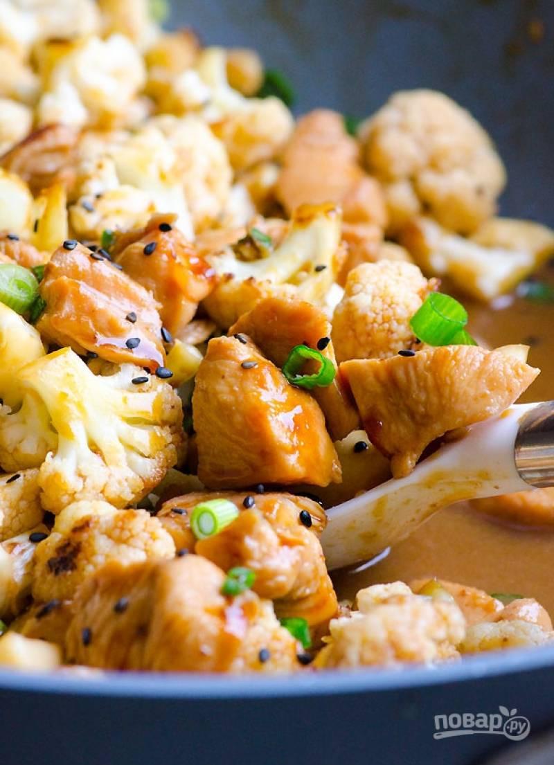 Затем добавьте обжаренную цветную капусту и протомите 5 минут. Посыпьте кунжутом и мелко нарезанным зеленым луком. Блюдо готово!