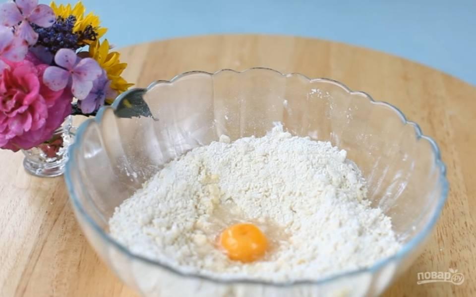 2.Высыпьте в миску муку, разотрите ее со сливочным маслом. Добавьте сахарную пудру, яичный желток и воду. Замесите тесто.
