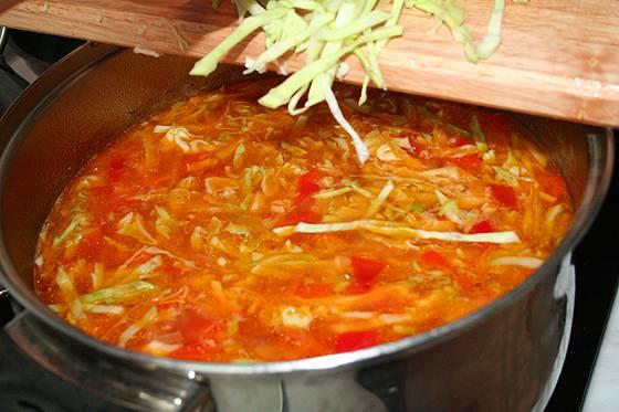 Обжаренные овощи добавляем в кастрюлю. Затем мелкой соломкой нарезать капусту и тоже отправить в кастрюлю. Варим все еще 5 минут.