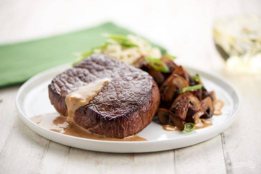 6. К грибам добавьте соль и перец по вкусу. Выложите стейк для подачи вместе с пюре и шампиньонами. Вылейте соус из сковороды на мясо. Приятного аппетита!