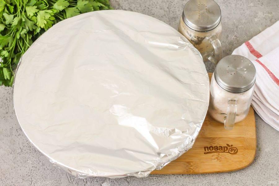 Накройте форму для запекания фольгой и поместите ее в духовку.